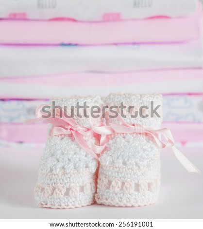 Baby girl pink shoes on the clothes background