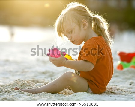 Baby girl play with sand. Koh Lipe island, Thailand - stock photo