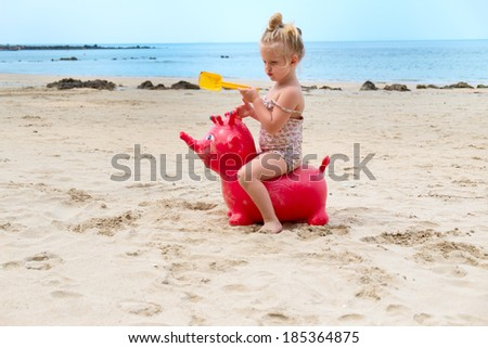 Baby girl playing at the beach - stock photo