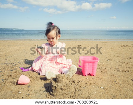 baby girl playing in the sandy beach,Northern Ireland