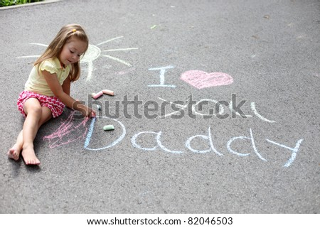 Baby girl playing on asphalt  with chalk.