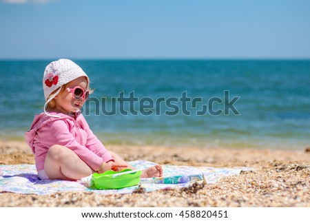 Baby girl playing on the beach near the sea on a hot day during the summer holidays