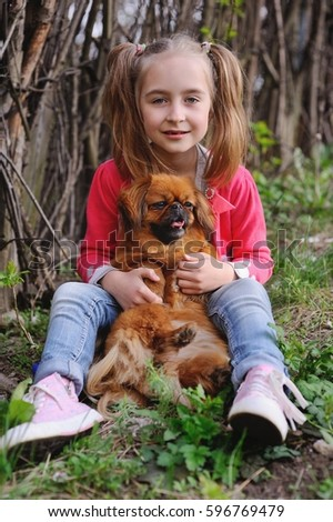 Baby girl playing with a puppy of a pekingese