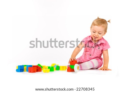 Baby girl playing with building blocks - stock photo