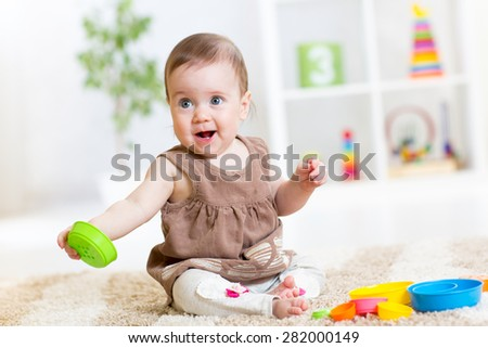 baby girl playing with colorful toys at nursery - stock photo