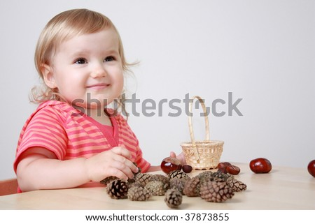 Baby girl playing with cones and chestnuts