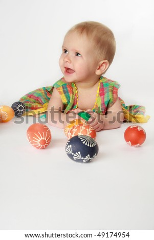 Baby girl playing with Easter eggs - stock photo