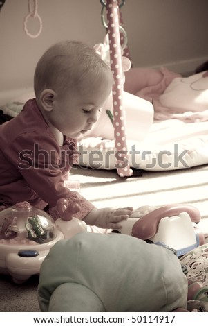 baby girl playing with her toy phone - stock photo