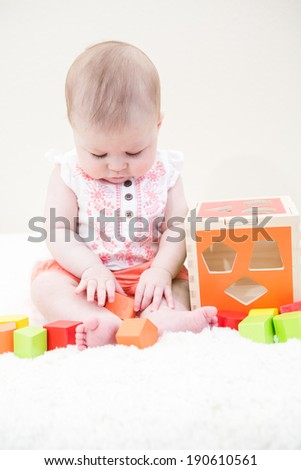Baby girl playing with her toys on a white blanket.