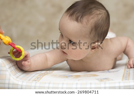 baby girl playing with rattle toy - stock photo