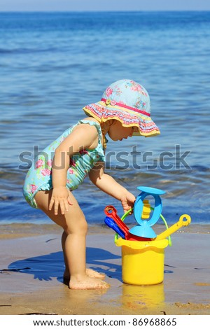 Baby girl playing with toys on the beach - stock photo