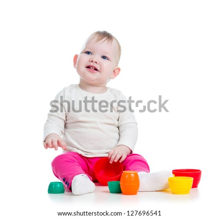 baby girl playing with toys while sitting on floor, isolated over white - stock photo