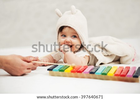 Baby girl playing with xylophone toy on blanket at home - stock photo