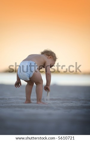 Baby girl plays with a sand
