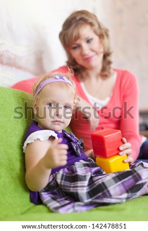 baby girl plays with blocks in home interior - stock photo