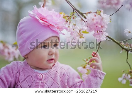 Baby girl portrait with sakura blossom - stock photo