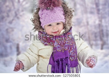 Baby girl's portrait on background of snowy forest - stock photo