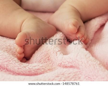 Baby Girl's Tiny Feet - stock photo