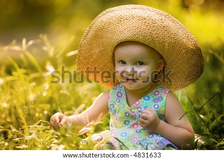 baby girl seating on the grass - summer - stock photo