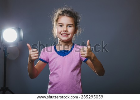 baby girl showing thumbs up sign yes - stock photo