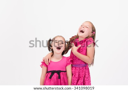 Baby girl sisters laughing aloud together in pink dress - stock photo