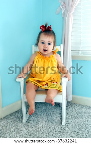 Baby girl sits on her white wooden rocker and rocks and coos.  She is wearing a bright yellow dress with embroidered chickens on it.  Her nursery is aqua and pink. - stock photo