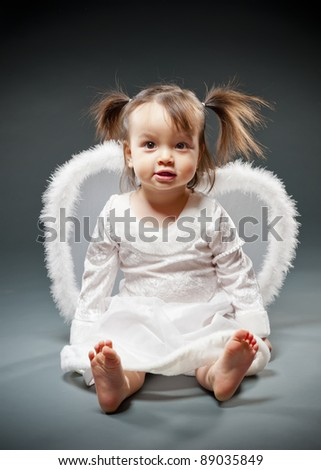 Baby girl sitting and dressed as an angel