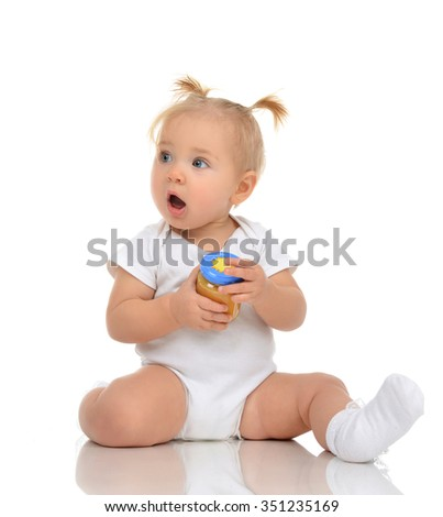 Baby girl sitting and holding jar of child mash puree food isolated on a white background