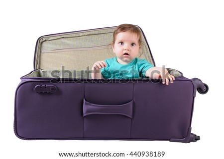 baby girl sitting in a purple suitcase on a white background - stock photo