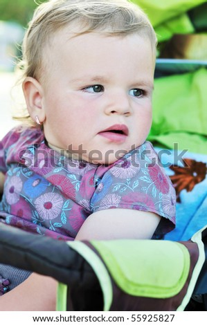 baby girl sitting  in the green stroller