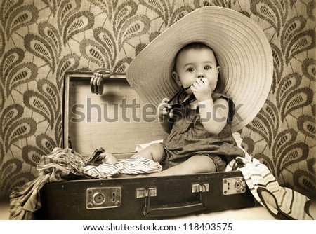 Baby girl sitting into the old suitcase retro image - stock photo
