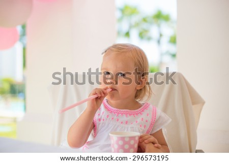 Baby Girl Sitting Next To Table With Pink Paper Cup and Straw