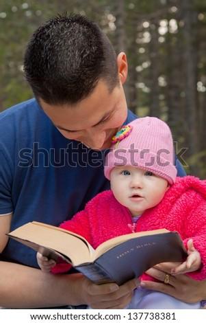 Baby girl sitting on dad�¢??s lap reading KJV Bible (King James Version) - stock photo