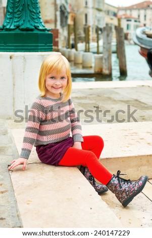 Baby girl sitting on embankment in venice, italy - stock photo