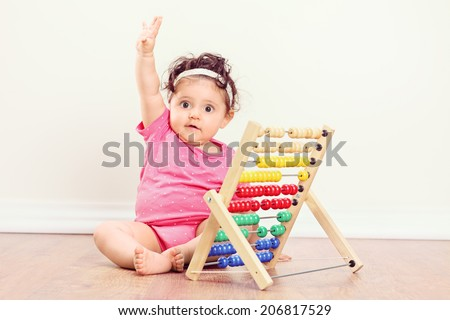 Baby girl sitting on floor and raising her hand with an abacus beside her - stock photo