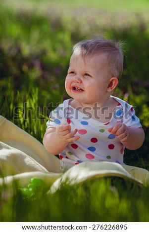 Baby girl sitting on green grass