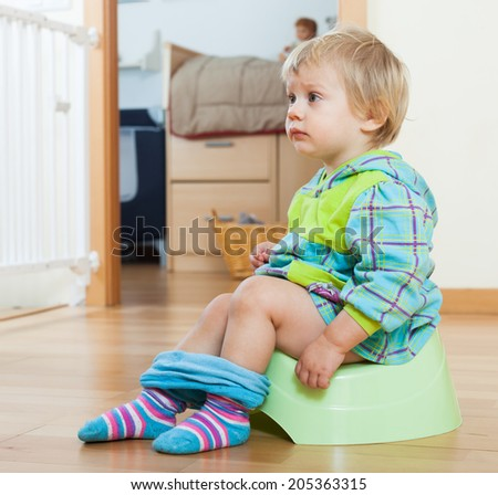 Baby girl sitting on green potty in home interior - stock photo