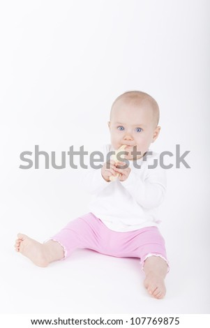 baby girl sitting on ground and eating a banana.
