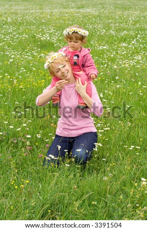 Baby girl sitting on her mothers neck wearing daisy wreath