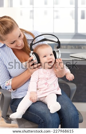 Baby girl sitting on mother's lap, listening to music through headphones, both smiling.