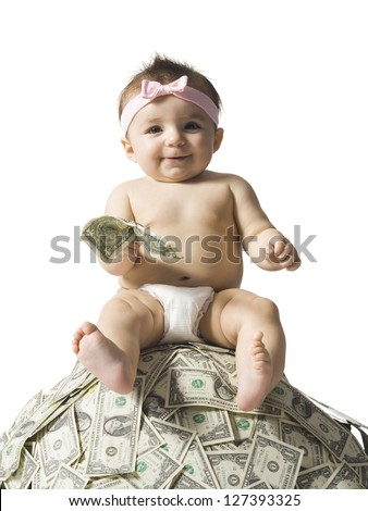 Baby girl sitting on pile of dollar - stock photo