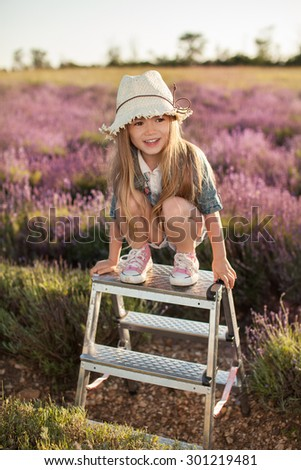 Baby girl sitting on top stepladder outdoors - stock photo