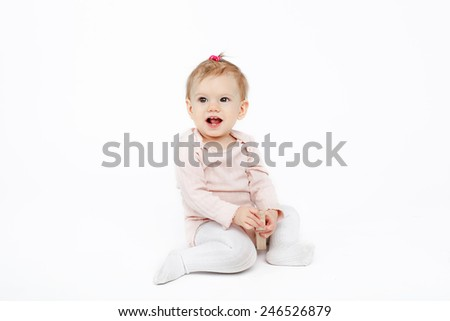 baby girl sitting with a wooden toy over white background in studio