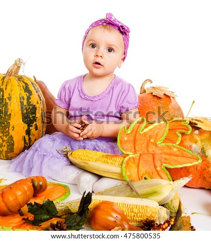 Baby girl sitting with autumn harvest - big pumpkins and corn
