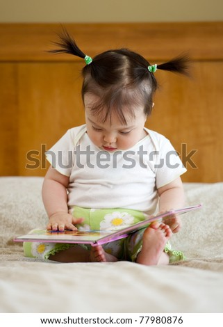 Baby girl sitting with opened book - stock photo