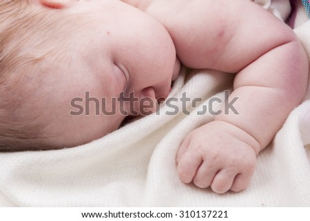 Baby girl sleeping in a white blanket - stock photo
