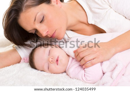 Baby girl sleeping with mother care near on white fur
