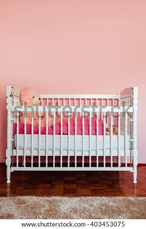 Baby girl sleeps in a crib covered with a pink blanket - stock photo