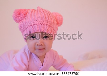 baby girl smileing in pink knitted bear hat on the bed