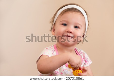 Baby Girl Smiling Holding Toy Looking at Camera - stock photo